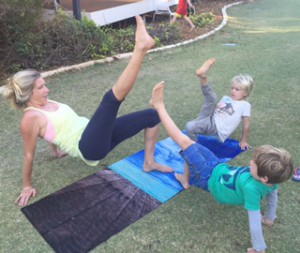 Kids Yoga Classes in Wembley. A mother and her 2 children practise yoga in a Wembley grass area