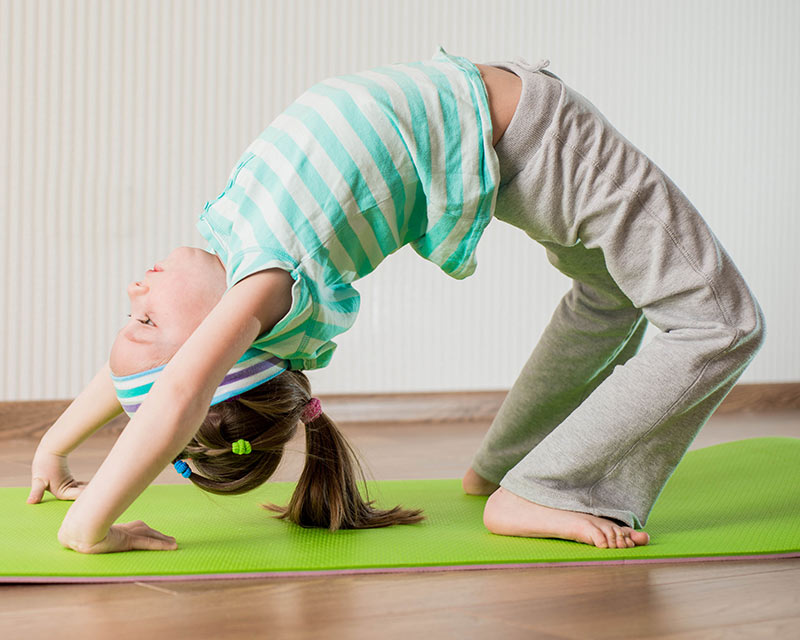 Kids Yoga classes in Wembley. A teenage girl and her two younger sisters are doing Yoga on a red mat.