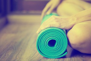 Be taught in one of the best yoga studios Perth. Lady rolling up green yoga matt